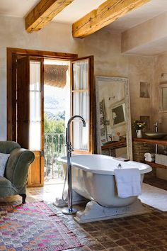 French doors, rustic beams, fabulous view, claw foot tub on awesome base, Juliet balcony, comfy chair all make for a fantastic bathroom!