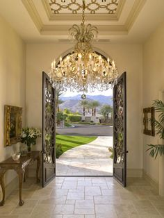 Custom ceiling design, a lavish chandelier and an iron front door evokes an Old World feel. With little maintenance, a high-quality metal door can stay beautiful for a lifetime.