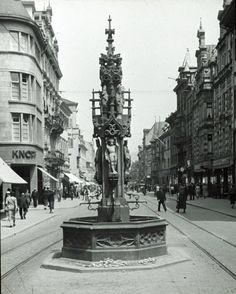Fischbrunnen Freiburg 1937    Sehr schöne Darstellung des Fischbrunnen Freiburg aus dem Jahr 1937. Der Fischbrunnen stand damals mitten auf der Kaiser-Joseph-Straße, die 1937 allerdings Adolf-Hitler-Straße hieß. Der Brunnen stand genau auf Höhe der Münsterstraße. Sein ursprünglich