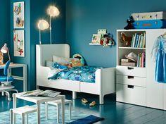 Blått barnerom med uttrekkbar seng, garderobe, bord og skrivebord i hvitt.