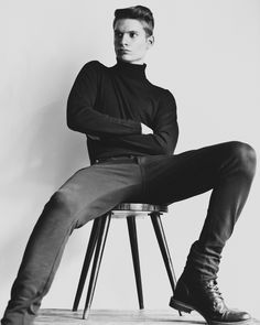 black 'n white picture of a male model with black turtleneck sitting on a stool