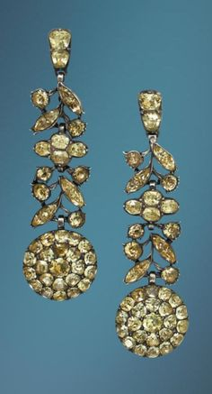 A pair of antique chrysoberyl pendent earrings, late 18th century/early 19th century. The articulated earrings of stylised foliate design, terminating in a circular cluster drop, set throughout with vari-cut chrysoberyls, foiled and closed-back settings throughout, mounted in silver, later hook fittings, length 7.2cm. #antique
