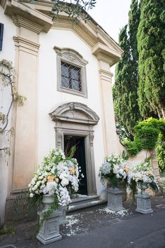Wedding church entrance decorations: flowers compositions in medici vases