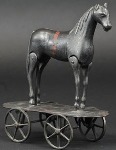 Circa 1895, japanned cast iron, classic Early American toy depicts horse in standing pose with articulated leg action when pulled along with spoke wheeled platform, has a folk art form.