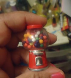 Base is a toothpaste cap, the container holding the gumballs is a plastic bottle from kid's nail polish. The top is from a medicine bottle and gumballs are sprinkles.