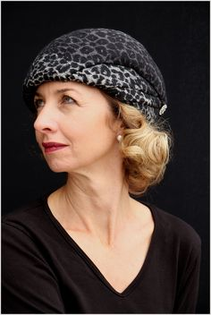 Snow leopard inthe city. This shaped beret embodies the exotic cat that is distinctive for its look and living in remote Asia. The classic muted colors of gray, black and white, appeal to yourd…