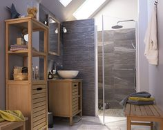 Castorama : Meuble de salle de bains Tinn. Des meubles en bois exotique et une lumière douce éclaire subtilement le carrelage sombre afin de conserver l'esprit zen de cette salle de bain.
