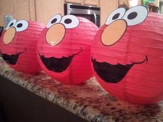Red paper lanterns decorated with the face of Elmo. See more Elmo birthday party ideas at www.one-stop-party-ideas.com