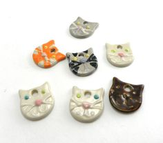 """7 Cat shaped stoneware pendants. Each pendant has been hand formed, hand glazed and high fired for durability. They measure 1"""" by 1""""  This set includes the following: White Cat with one blue eye and one green eye x2 White cat with green eyes Gray cat with yellow eyes Orange tabby with yel..."""
