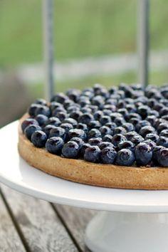Délicieuse recette de tarte aux myrtilles de Christophe Adam. Une pâte sucrée recouverte de miette de spéculoos, de myrtilles cuites recouvertes d'un flan et de myrtilles fraîches. #myrtilles #speculoos #nathaliebakes