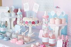 This traditional gender reveal party uses pink and blue scrap book paper as the backdrop for the dessert table.