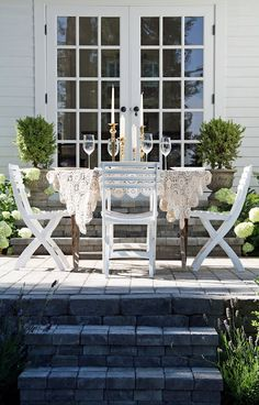 A Country Farmhouse. French door. Fancy Candle sticks and table cloth. Hydranges. Little limelights, Box woods.