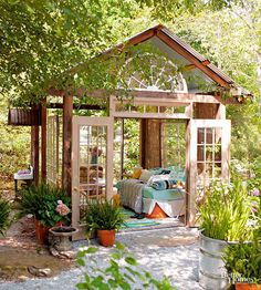 Need a relaxing escape? Build one in your own backyard. This outdoor room features French doors, suspended divided-light windows, and a corrugated-metal roof—creating the impression of a fully enclosed space. Inside, a bed offers the perfect spot for an afternoon nap./