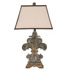 Fleur-de-lis-shaped table lamp in antiqued gold. Product: Table lamp  Construction Material: Resin  Color: Antique gold   Accommodates: (1) Standard bulb - not included    Dimensions: 30.5 H x 8.5 W x 5 D     Cleaning and Care: Wipe clean with damp cloth