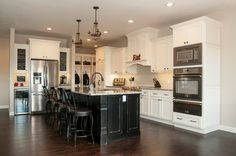 maple kitchen with black island | Maple cabinetry painted off white with a dark glaze, a rubbed black ...