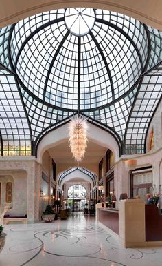 Opulent Lobby at Four Seasons Hotel Gresham Palace Budapest. The Lobby is grand, with a dramatic, arching cupola, stained glass and a mosaic floor, and signals both the richness of the structure's history and the splendor of its current incarnation. An entrance that makes a statement in its own...