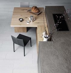 Cloe kitchen by Cesar cucine, particular of the table that connects harmoniously to one of the natural knotted oak shelves that run along the island unit, offering an original and elegant solution that optimises the space available. TOGNIN ARREDAMENTI authorized dealer.