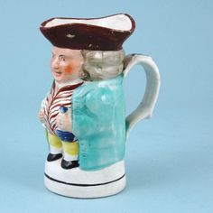 19th century Staffordshire pottery minature Toby Jug with turquoise jacket and brown hat.