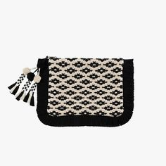 Black and white fringe tassel clutch with pom pom detail. This versatile four season globally inspired clutch is accented with a festive fringe.
