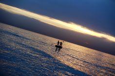 Dua remaja Palestina mencari ikan dengan berperahu saat matahari terbenam di kota Gaza.