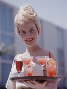 Cocktail waitress, 1960s ... but change hair color, uniform, and place to not so wholesome looking like this