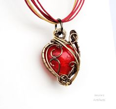 This is a custom order.I used enameled copper wire in gunmetal and gold colourto wrap a red lampwork glass heart bead.Pendant measures 3.4cm My Etsy Shop --> www.etsy.com/shop/ianira