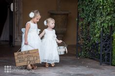 "Flower girls walk down the aisle in the Piazza Toscana courtyard while wearing white dresses with white flowers in their hair, and holding a wood sign ""Uncle Scott here comes your bride"" 