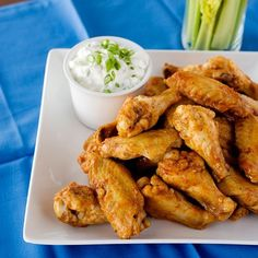 Most of us think of Buffalo wings as bar food, but with their accompaniment of celery sticks and creamy blue-cheese dressing, they make a fine casual meal. These wings are hot, but if you like them incendiary, pass extra Tabasco sauce at the table.