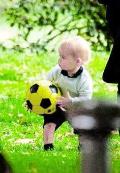Prince George plays with a ball in the park under the watchful...