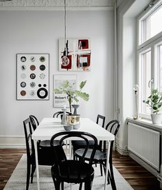 Dining: white rectangular dining table with mismatched black dining chairs (incl Thonet bentwood), pale grey walls, white cornices, exposed lightbulb pendant light, timber floorboards