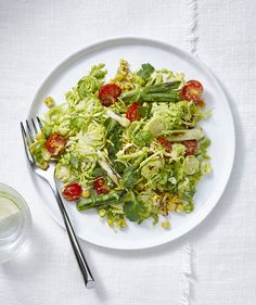 Swap traditional cabbage coleslaw for a Brussels sprouts version tossed in a light and creamy avocado-cilantro dressing. Cherry tomatoes, scallions, and smoky corn freshen up this picnic classic—but when it's not in season, frozen sweet corn is a fine substitute.