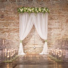 Dress up a modern loft with draped fabric and flowers. Beautiful wedding ceremony backdrop!