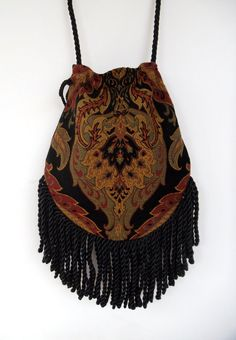 Fringed Gypsy Tapestry Bag. Its got that boho look but is also feels a bit renaissance with the rich chenille tapestry . Black with gold, ,sage green and rust. The back is a solid black cotton velvet. It is lined with a black cotton blend.. It is a drawstring bag with a black twist cord.  Inside it has a pocket. Big enough for keys or phone.  The bag itself is 11 wide (at the widest point) and it is 12 long plus the 5 fringe making it a total of 17 long.11 wide. The strap is a black twist…