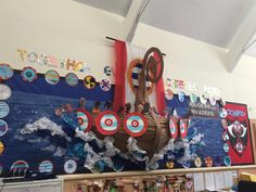 Viking classroom display KS2. Constructed with a cardboard frame and clad in paper. Pictures of kids on 'bobbleheads' are in the boat (faces blurred out)