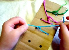 Simple knot tying practice for kids- a piece of cardboard , a hole punch, and yarn
