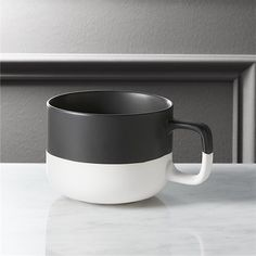 Shop black dip coffee mug.   Two-tone stoneware mug pulls a double.  Demi-dipped in matte black glaze, low-profile form with square handle exposes the natural clay base to graphic effect.
