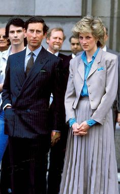 Princess Diana circa 1986, in a grey pleated skirt suit, with Bolero length short jacket, turquoise polka dot blouse, turquoise handkerchief in her jacket pocket.  Princess Diana also wore this outfit to Stoke Mandeville hospital 1986 (B&W pic, different earrings: gold stud earrings ).