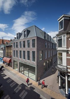 Shop and student residence building by Dreessen Willemse Architecten, Utrecht, The Netherlands. The building has a deep, grey ridged roof with protruding dormer windows and a facade made up of slim red bricks. Brick Facade, Facade House, Building Exterior, Brick Building, Brick Architecture, Residential Architecture, Mansard Roof, Facade Design, Modern Buildings