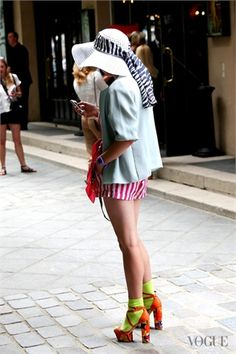white wide hat , light blue jacket over red and white shorts, orange heels and yellow socks at Paris Haute Couture - Vogue.it