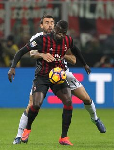 M'Baye Niang of AC Milan competes for the ball with Andrea Barzagli (back) of Juventus FC during the Serie A match between AC Milan and Juventus FC at Stadio Giuseppe Meazza on October 22, 2016 in Milan, Italy.
