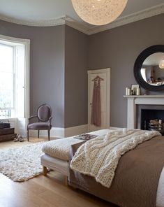 174514554284721521 Cozy contemporary bedroom with warm colors. Love the round mirror above the fireplace.