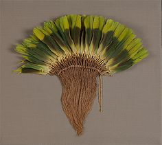 NAZCA culture South coast 100 – 700 AD Plume 100-700 AD feathers and vegetable fibre The green plume, possibly a fan or crown ornament, is made from the glorious three-toned tail feathers of the Amazon parrot.  These colours occur naturally, while that of the yellow and pink-orange plume: was obtained by 'tapirage'.Parrots, macaws and ducks were probably domesticated, as their bones and mummified bodies have been found in archaeological excavations. Most prized of all was the Scarlet Macaw.