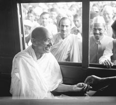 Gandhi receives a donation in a train compartment in 1940. Acharya Kripalani and Radhakrishna Bajaj are looking in through the window.