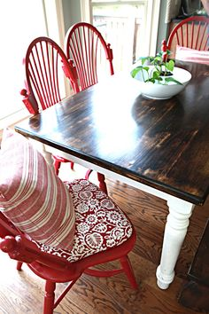 Loving everything about this dining table...antique stained top, white base, red chairs =