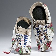 native american, America, Sioux beaded hide moccasins, sinew-sewn and beaded using colors of white, dark blue, pea green, and red white-heart; with long forked tongues terminating in tin cones and dyed horsehair, fourth quarter 19th century.