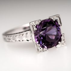 This pretty vintage amethyst ring is centered with old Euro cut purple amethyst weighing 2.6 carats. The stone is set into a square illusion style head that features etched designs down the prongs. The sides and shoulder are also etched for beauty. The ring Is crafted of solid 18K white gold and is in very good condition.