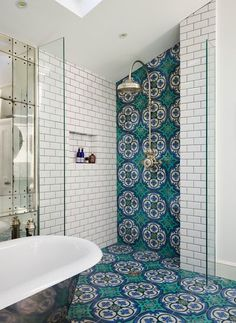 Absolutely love this bathroom with white subway tile, Moroccan tiles along the floor and shower, stainless steel oversized shower head and a metallic freestanding tub