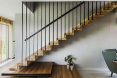 The minimalist staircase and its metal rod railing seem to be inspired by the house's facade design Staircase Design Modern, Modern Stairs, Railing Design, Facade Design, House Design, Modern Design, Wood Stairs, House Stairs, Facade House