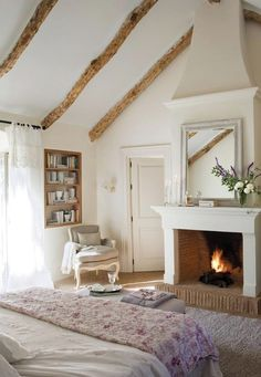 A bedroom with a fireplace and bookshelf in the wall. Love the high ceiling and exposed beams!