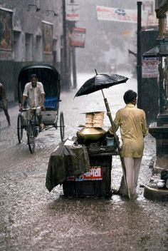 Steve McCurry: Chandni Chowk, Old Delhi, India. 1983. A food vendor in the rain